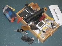 Eine Holzkiste gefüllt mit vielen Schlüsseln, einem Regenschirm, einem Handy und einem Etui.