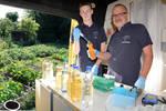 Milan Toups und Harald Gülzow entnehmen einer Wasserflasche eine Probe